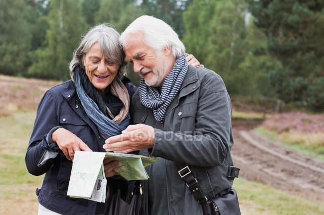 Coppia anziana guardando la mappa nella foresta durante il giorno — Foto stock