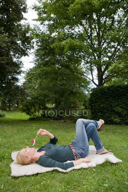 Жінка розслабляючий на підодіяльнику у траві — стокове фото