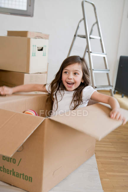 Chica sonriente jugando en caja de cartón - foto de stock