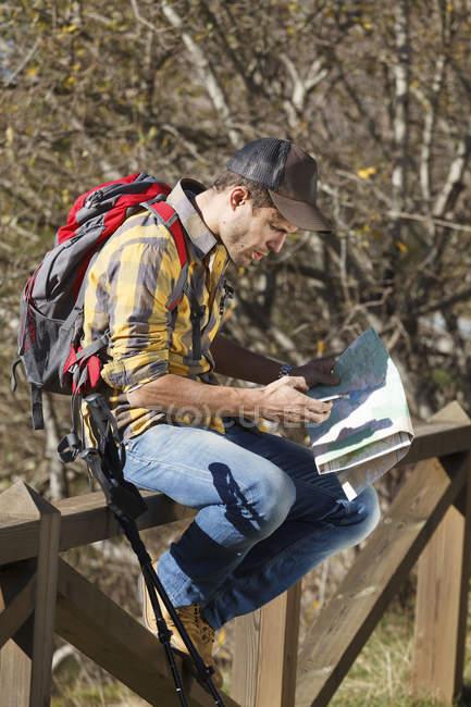 Hiker reading map on wooden handrail, Montseny, Barcelona, Catalonia, Spain — Stock Photo