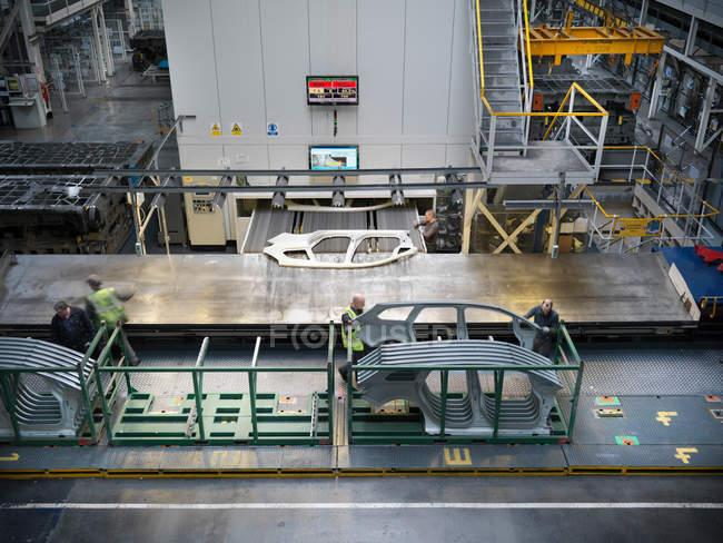 Vista de ángulo alto de los trabajadores que manejan piezas de automóviles como salen de la prensa en la fábrica de automóviles - foto de stock