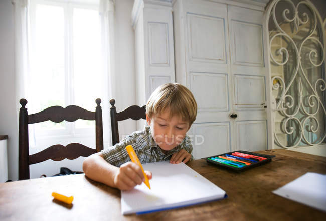 Boy with drawing sitting at the table at home — Stock Photo