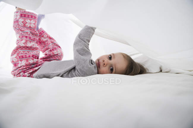 Portrait of female toddler lying between white bed sheets — Stock Photo