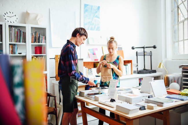 Young craftswoman and man in creative print studio — Stock Photo