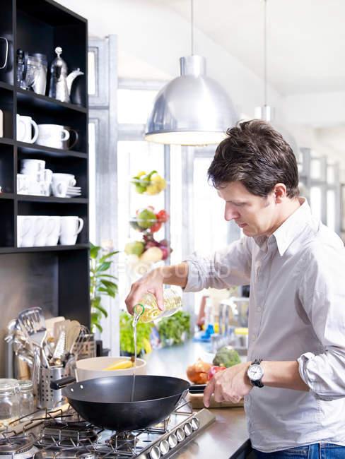 Людина в кухні приготування їжі з wok — стокове фото