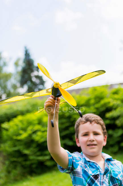 Boy playing with toy airplane outdoors — Stock Photo