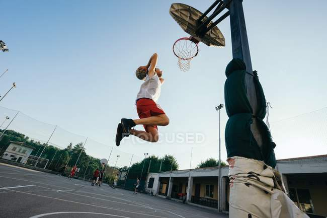 Man jumping to basketball hoop on playground — Stock Photo