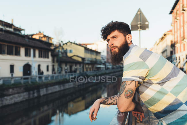 Man leaning against railing by canal — Stock Photo