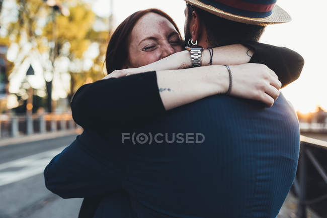 Couple hugging each other on sidewalk — Stock Photo