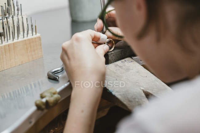 Over shoulder view of female jeweller making ring at workbench — Stockfoto