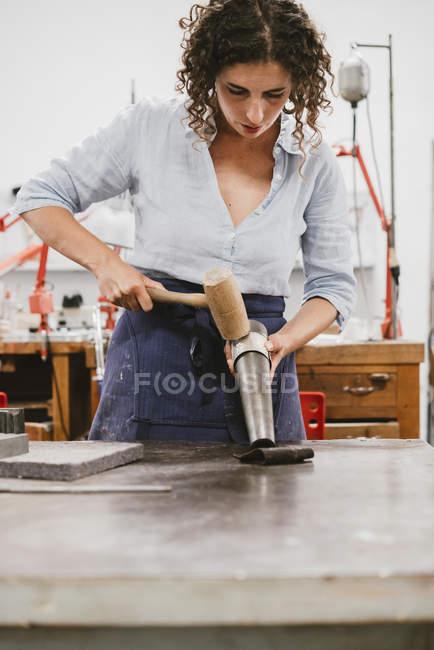 Female jeweler hammering bangle at workbench — Stock Photo