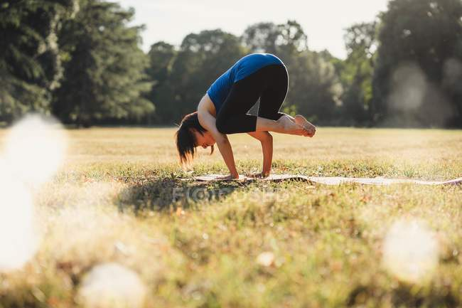 Mature woman in park, balancing on hands, in yoga position — Stock Photo