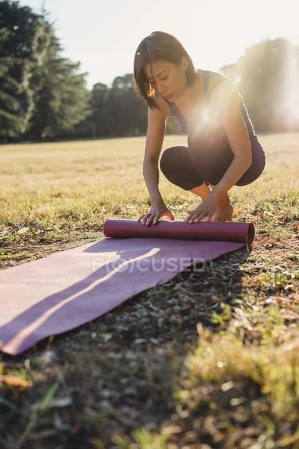 Femme d'âge mûr dans le parc, rouler les tapis d'yoga — Photo de stock