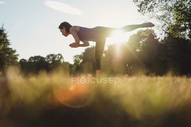 Femme d'âge mûr dans le parc, en équilibre sur une jambe, en position d'yoga, faible angle vue — Photo de stock