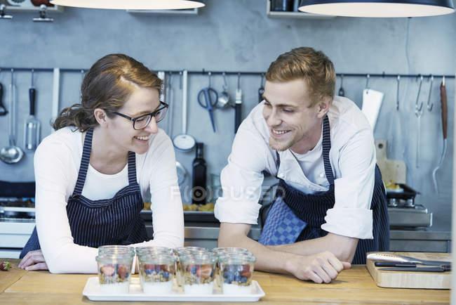Два повара, глядя на лоток готовой ягод десерты — стоковое фото