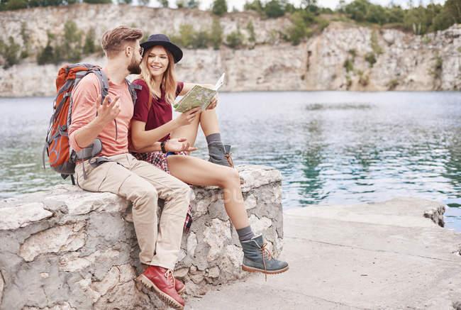 Пара, сидящая на стене у воды, глядя на карту, Мбаппе, Малопольские, Польша, Европа — стоковое фото