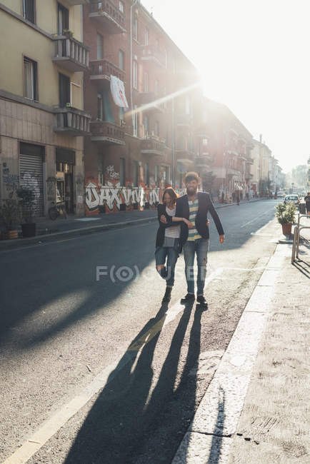 Happy couple strolling down sunlit street — Stock Photo