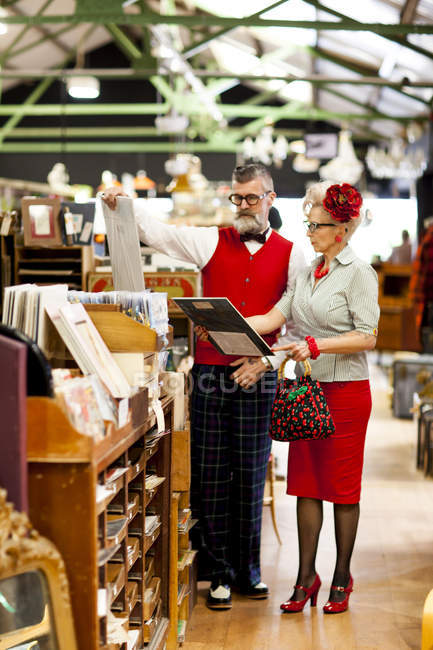 Quirky vintage couple looking at pictures in antique and vintage emporium — Stock Photo