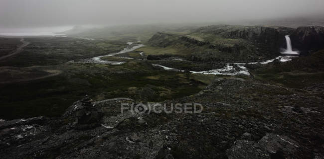 Waterfall and river in rocky landscape — Stock Photo
