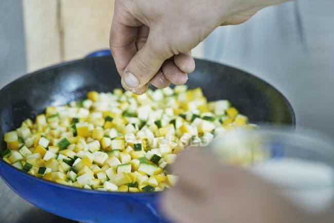 Imagem recortada Chef tempero legumes na frigideira — Fotografia de Stock