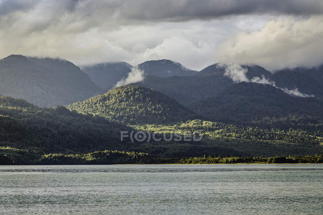 Mist rising from mountains over Lake Verde, Queulat National Park, Chile — Stockfoto