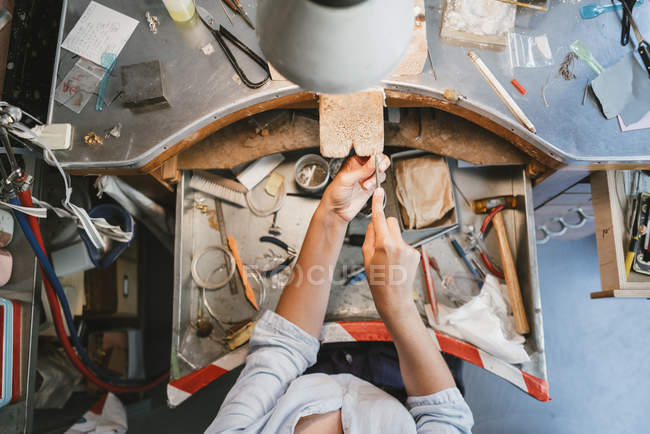 Overhead view of female jeweller's hands working at workbench — Stock Photo