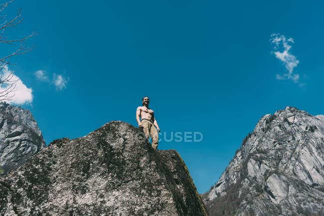 Низький кут зору голими грудьми чоловік, що стоїть на вершині Боулдер — стокове фото