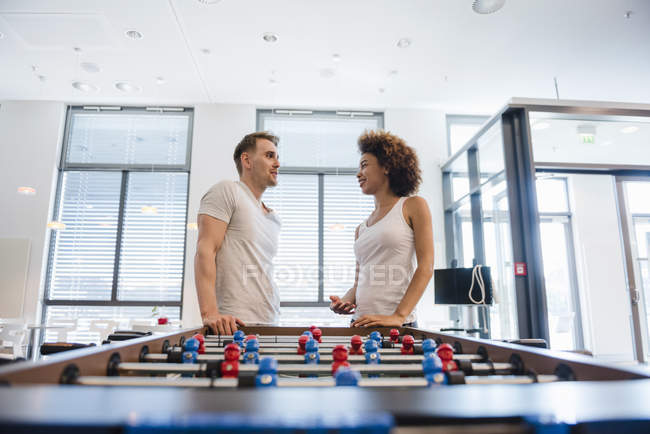 Couple leaning against football table and chatting — Stock Photo