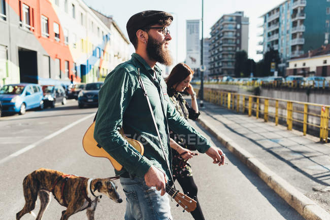Couple cool chien de promenade par canal de la ville — Photo de stock
