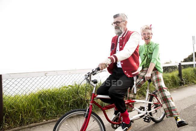 Senior couple sightseeing on tandem bicycle — Stock Photo