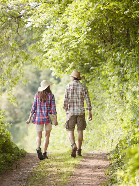 Rear view of couple in hats walking along track — Stock Photo