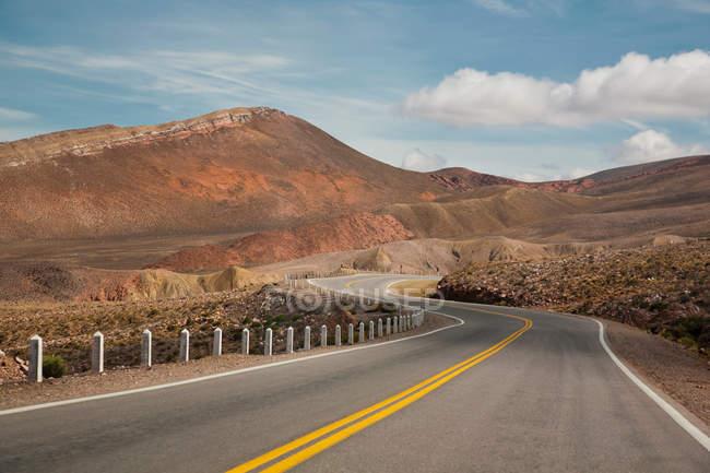Estrada vazia, passando por belas montanhas — Fotografia de Stock