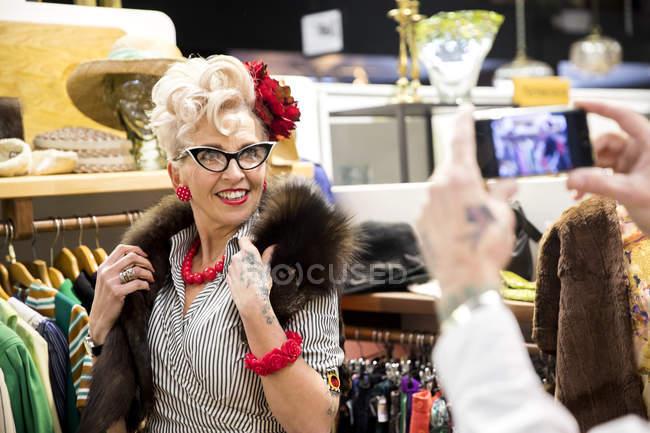 Homem fotografando vintage mulher madura na loja de roupas — Fotografia de Stock