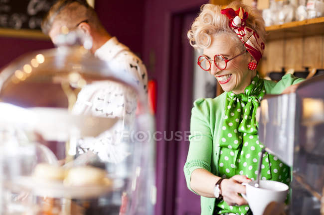 Quirky vintage woman using coffee machine in tea room — Stock Photo