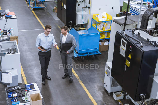 High angle view of two male managers with clipboards talking in factory — Stock Photo