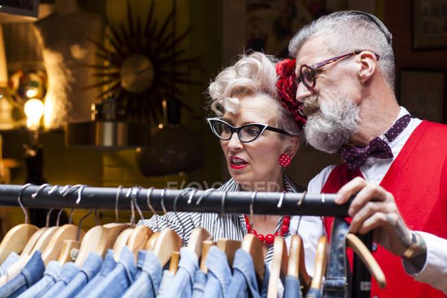 Quirky casal vintage olhando para trilhos de roupas em antiguidades e empório vintage — Fotografia de Stock