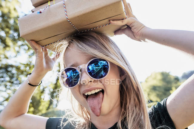Menina colando a língua para fora com caixa na cabeça — Fotografia de Stock