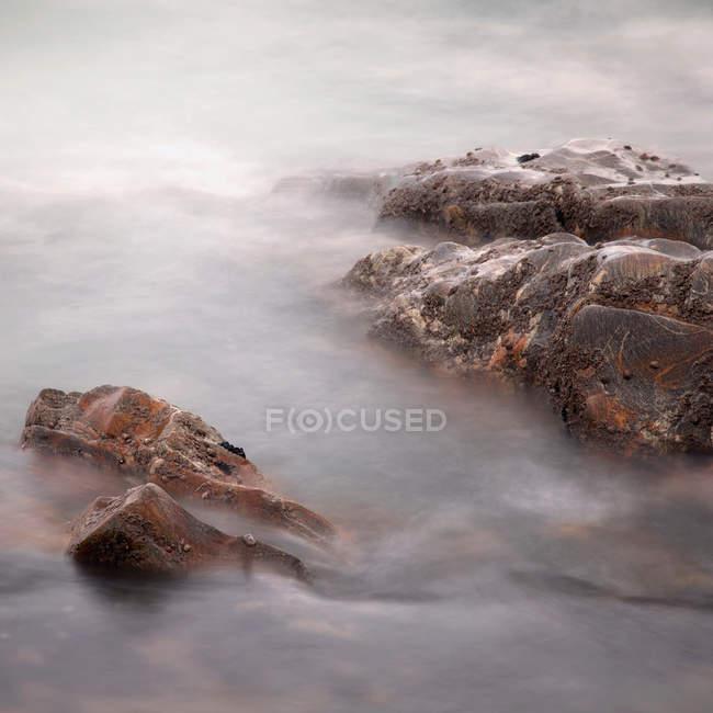 Vogelperspektive Blick auf ätherische natürlichen Blick auf Felsen im Meer bei Nebel — Stockfoto