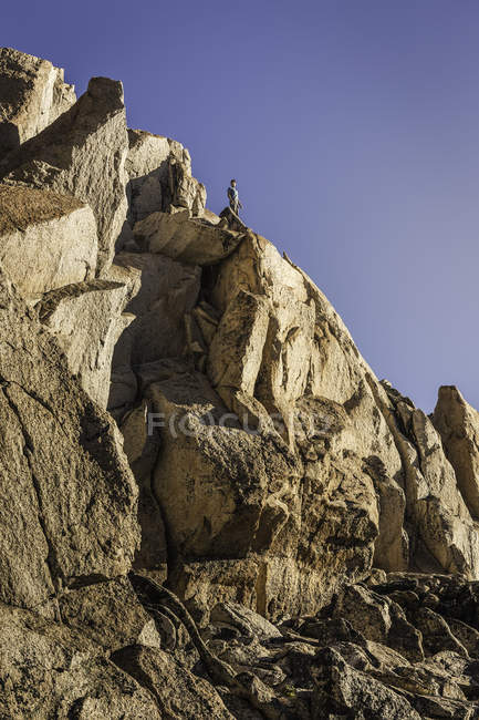 Чоловічий альпініст, дивлячись з вершини міцний кам'яної скелі, Анд, Науель Хуапі Національний парк, Ріо-Негро, Аргентина — стокове фото