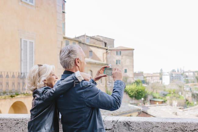 Tourist couple photographing cityscape, Siena, Tuscany, Italy — Stock Photo