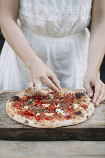 Cropped image of Woman putting ingredients on homemade pizza — Stock Photo