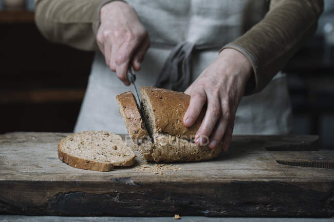Woman slicing bread on chopping board, mid section — Stock Photo