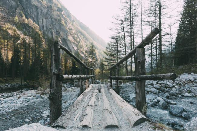 Pasarela de madera cruza la montaña río, Mello, Lombardía, Italia - foto de stock