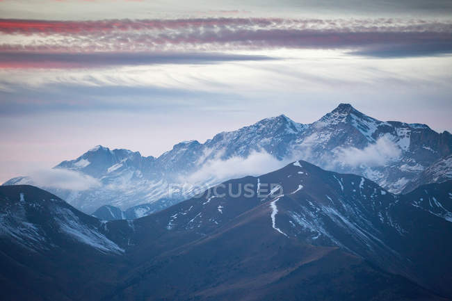 Majestic landscape with fog rolling over mountains and cloudy sky at sunset — Stock Photo
