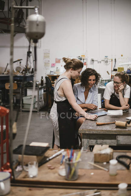 Three female jewelers looking at digital tablet at workbench — Stock Photo
