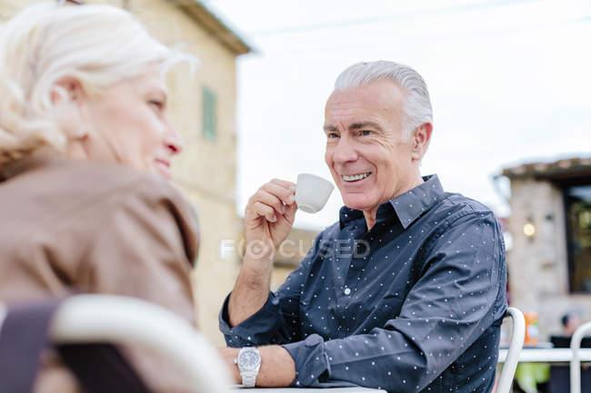 Вид на плечо туристической пары, пьющей эспрессо в кафе на тротуаре, Сиена, Тоскана, Италия — стоковое фото