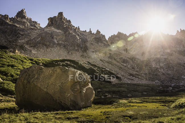 Boulder en Valle de la montaña iluminada por el sol, Parque Nacional Nahuel Huapi, Río Negro, Argentina - foto de stock