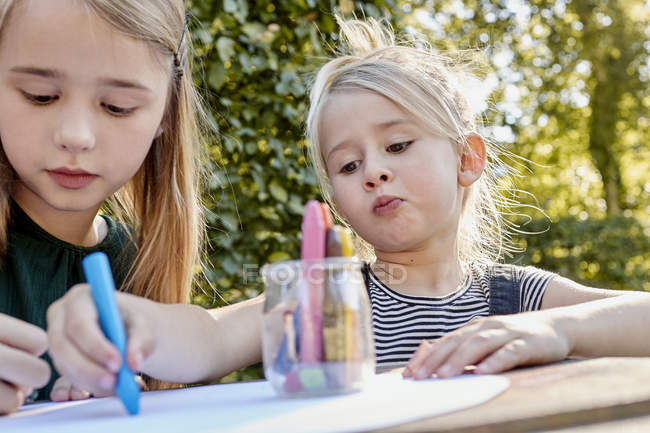Sisters colouring out in garden — Stock Photo