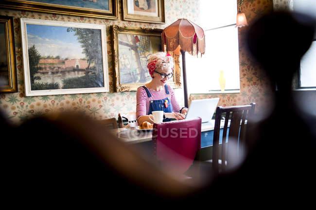 Вигадливий жінка, використовуючи ноутбук у барі-ресторані Борнмут, Англія — стокове фото