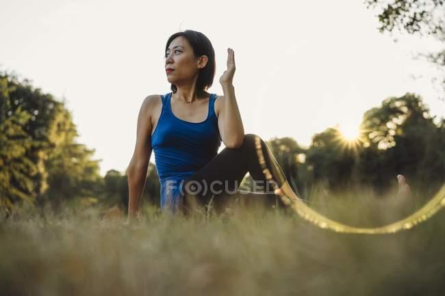 Femme mature en plein air, assis en position d'yoga, faible angle vue — Photo de stock